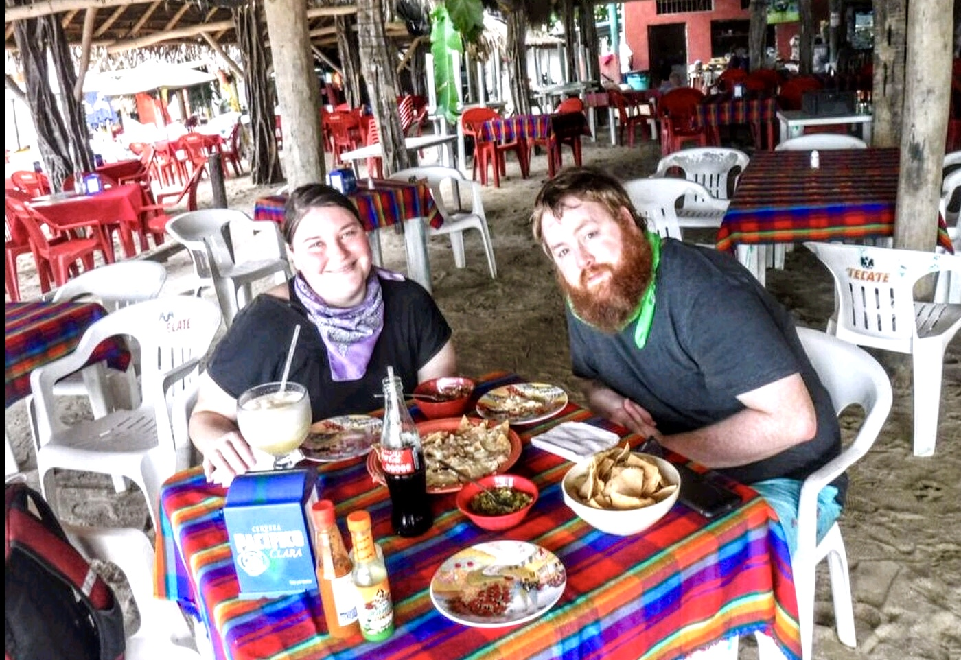 Scott and I at a beach restaurant having drinks and nachos, in a fishing village