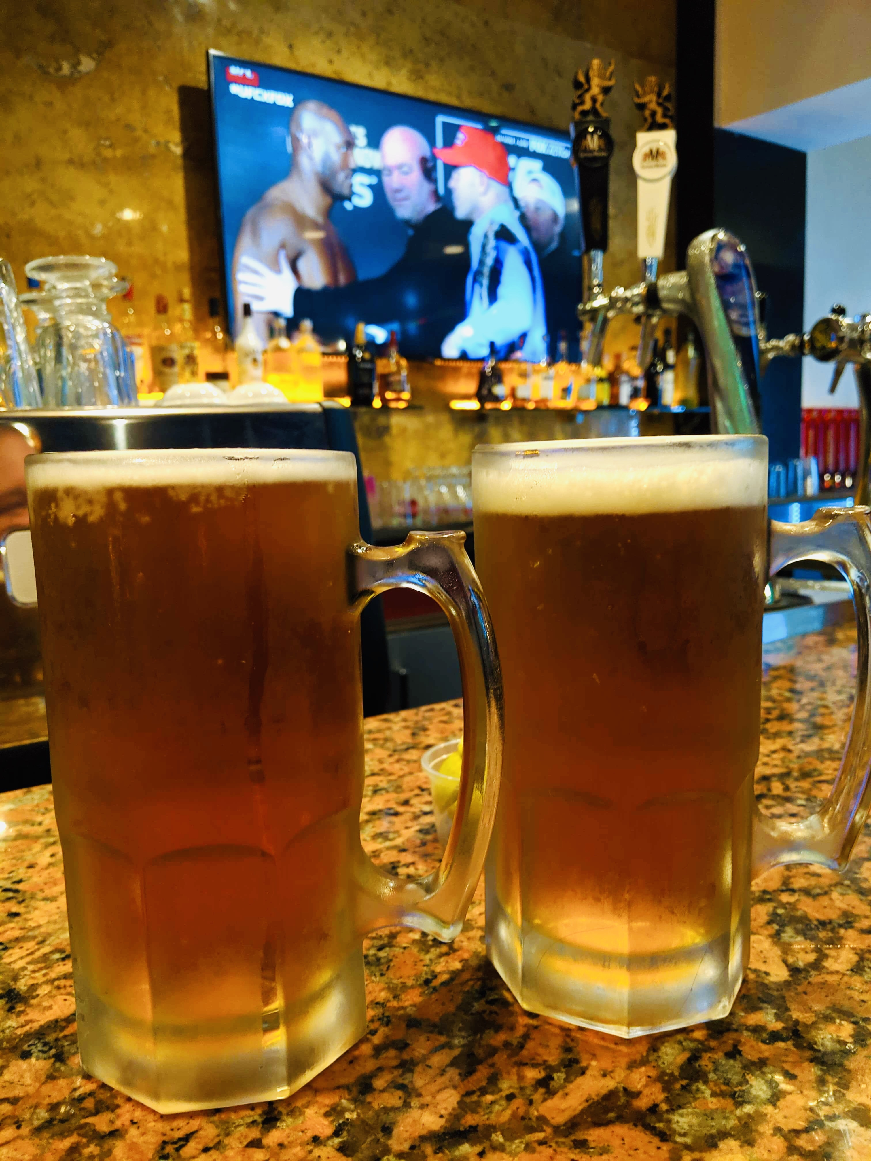 Two chilled pints of beer at the bar of Champions, with UFC playing on the screen in the background