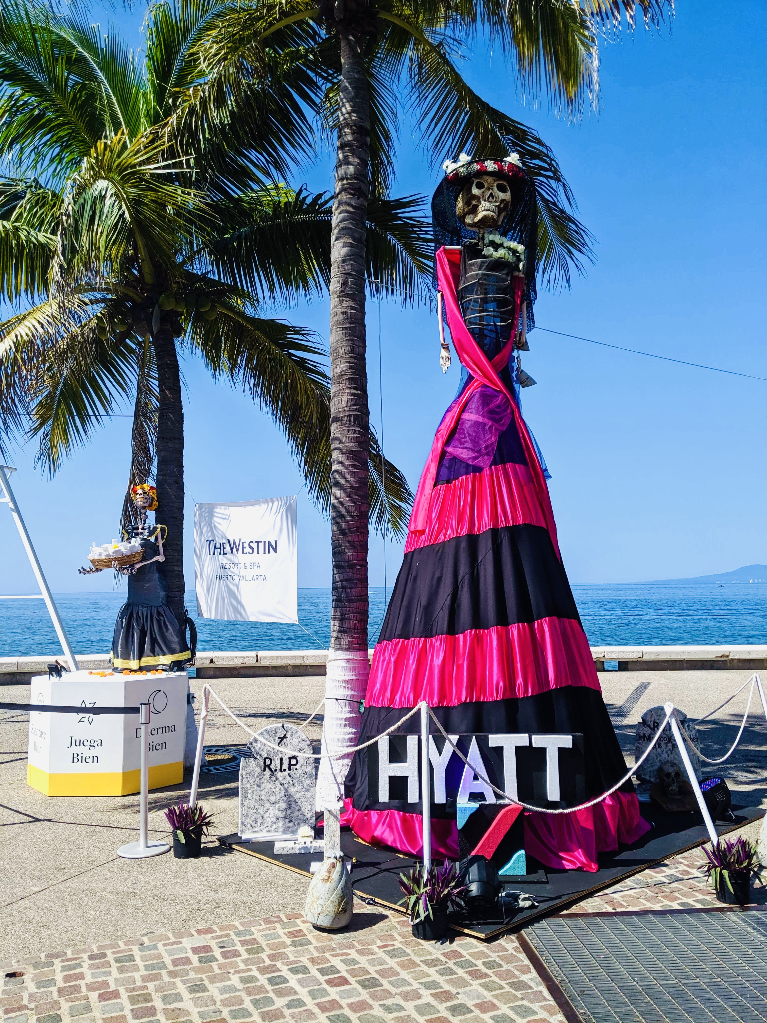 Hyatt Day of the Dead skeleton dressed up on Malecon, with ocean in background. Best places to spend Dia de Los Muertos