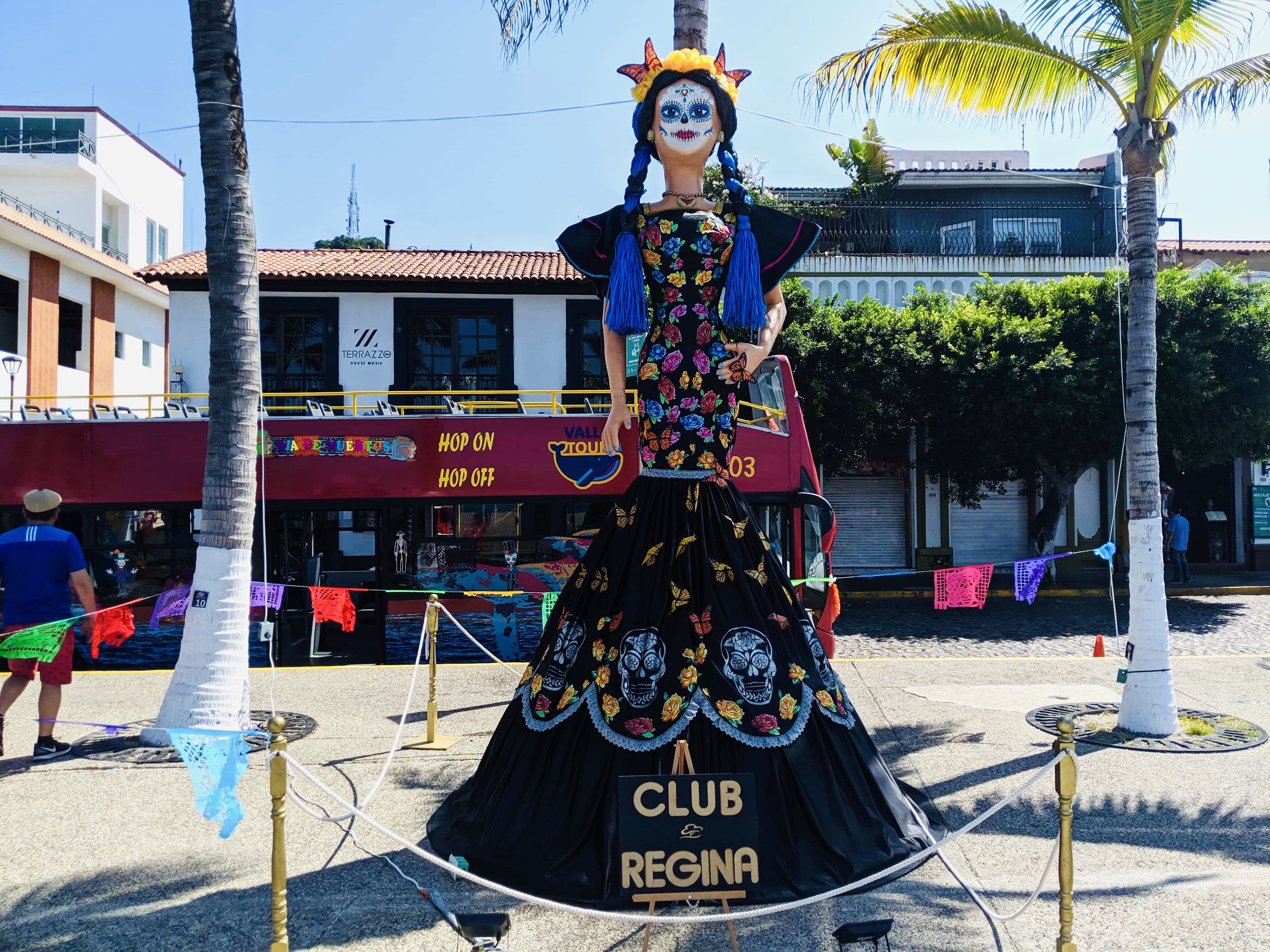 Club Regina Day of the Dead skeleton dressed up on Malecon, with shopfronts in background