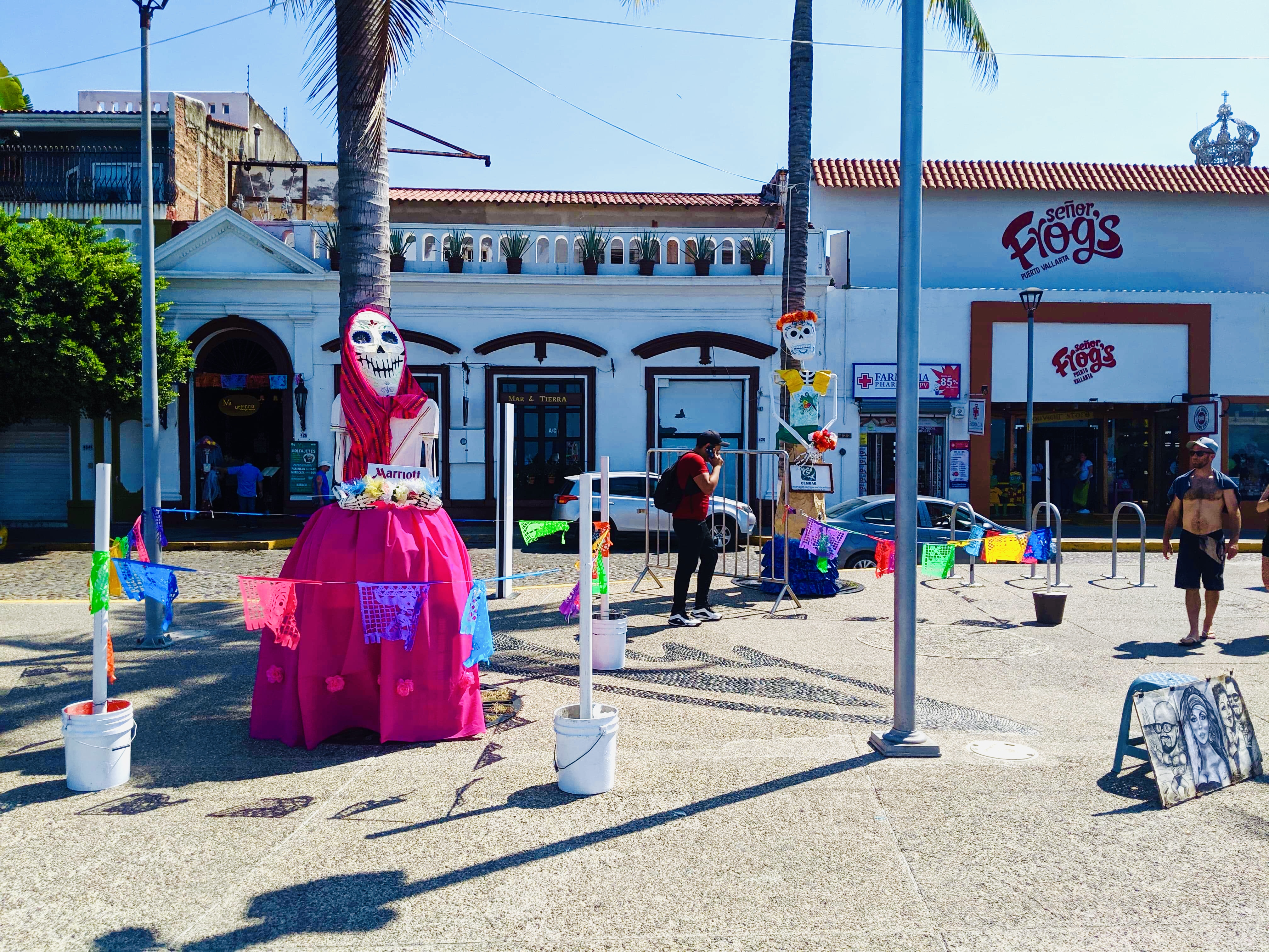 Marriott Day of the Dead skeleton dressed up on Malecon, with shopfronts in background