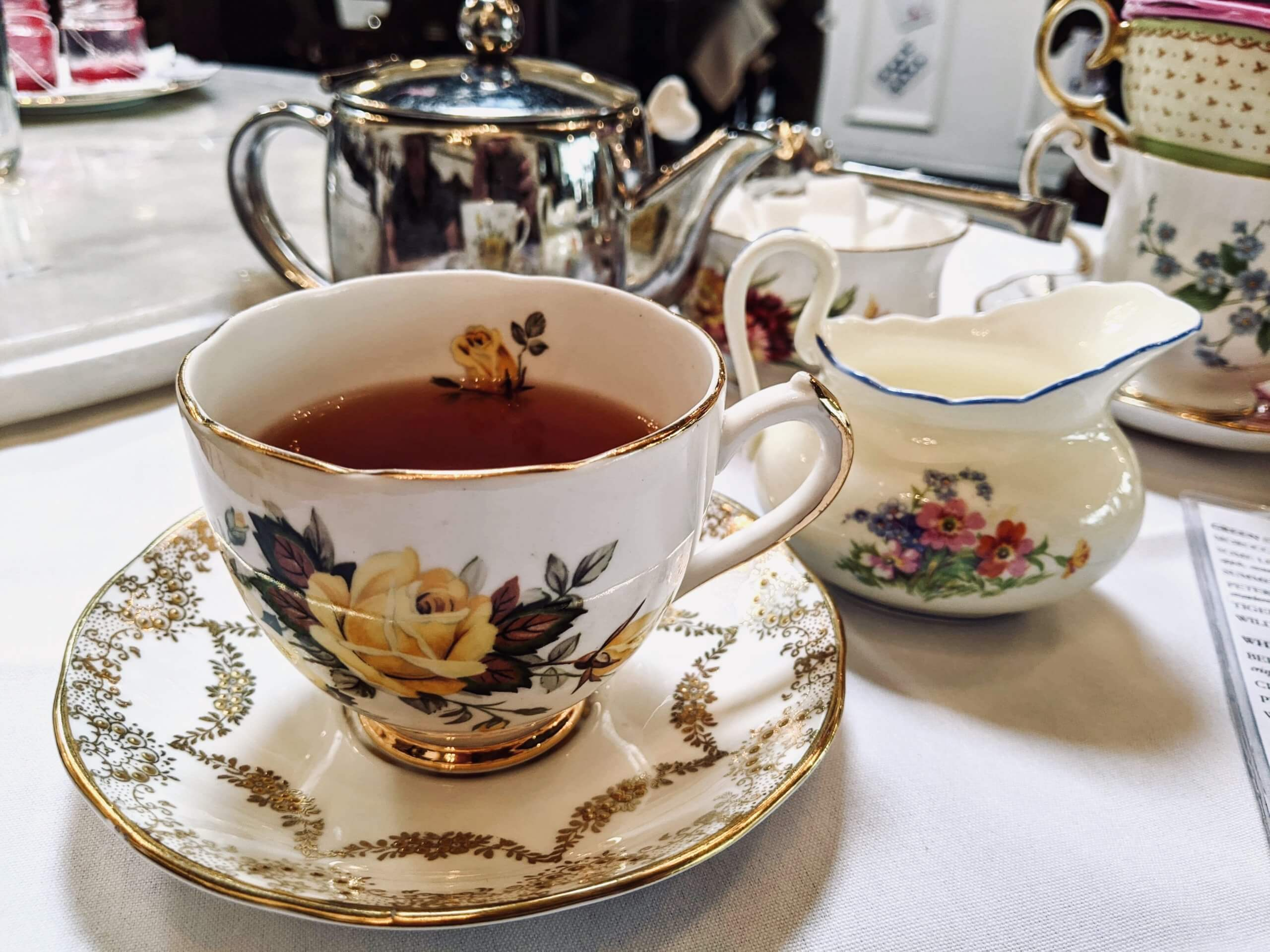 Tea cup, filled with tea, with the pot and sugar, milk, and honey in the background