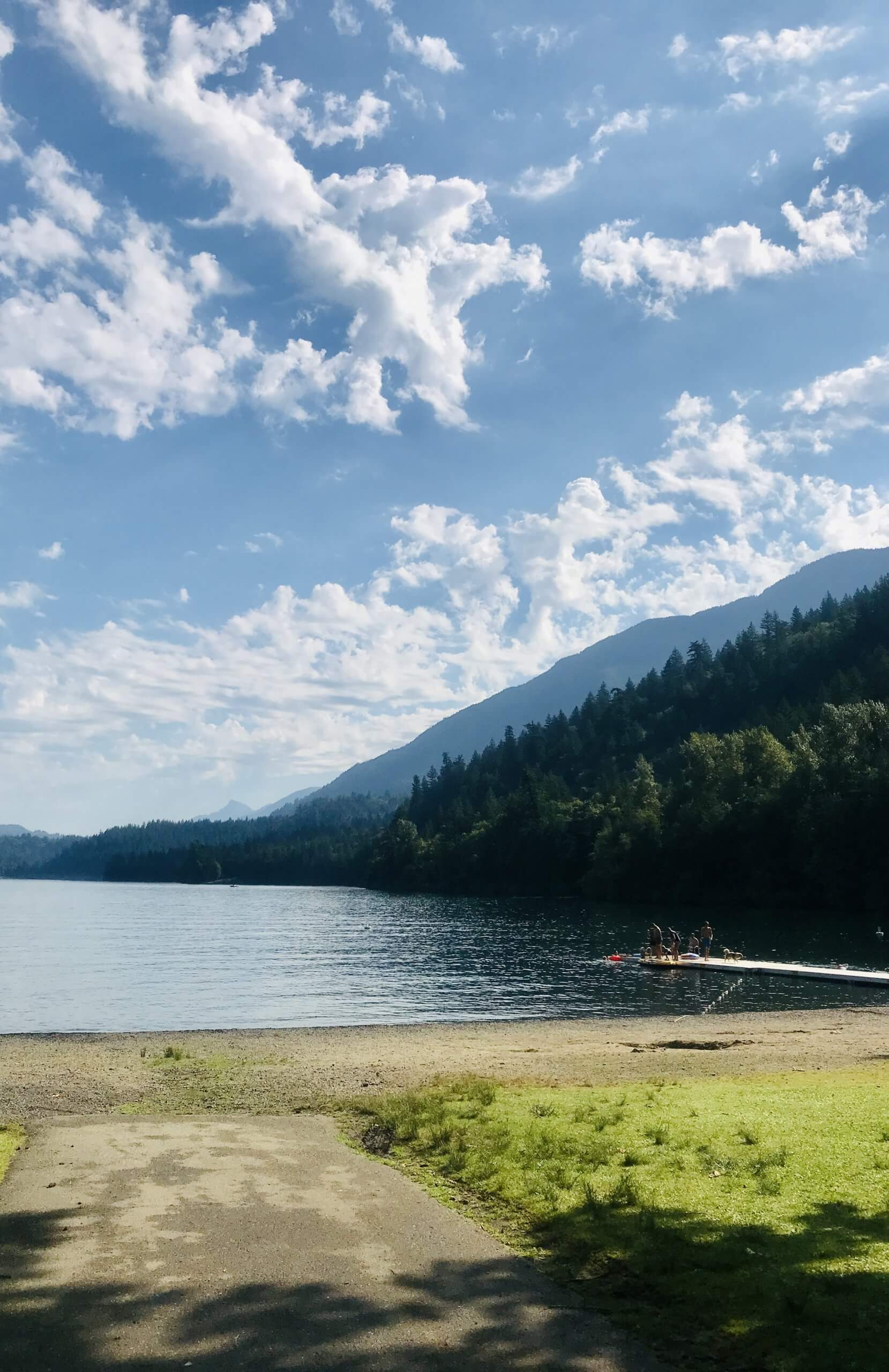 Cultus Lake, with blue skies, white clouds, the beach and crystal clear lake
