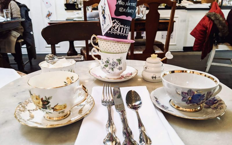 Two tea cups with our utensils and a mad hatter display